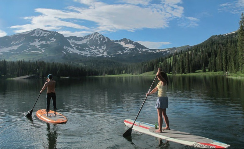 Paddle boarding in colarado. Image shows 2 people doing sup in awesome colorado scenery